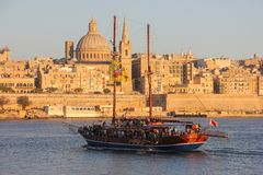 Wooden ship with tourists sailing in Grand Harbour of Valletta during sunset royalty free stock photo