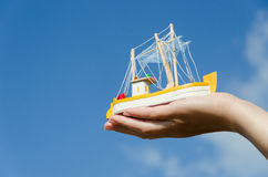 Wooden ship toy on palm on blue sky background Royalty Free Stock Images