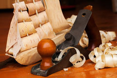 Wooden ship toy workshop carpenter with a plane Stock Photo