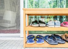 Wooden shoes rack at the house door Royalty Free Stock Images