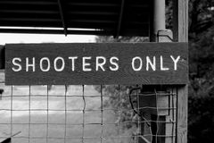 Shooters Only Sign. Wooden shooters only sign posted on metal fence on shooting range in a sportsman`s park Royalty Free Stock Image