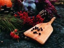 Wooden shovel cooking. Wood woodwork showel Cooking forest outdoor pepper cones Spruce kitchen pumpkin pumpkins berries Stock Photo