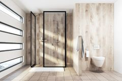 Wooden shower and toilet. Wooden shower interior with a tiled wooden floor, a rug, a toilet, an originally shaped window and a towel. 3d rendering mock up Royalty Free Stock Photo
