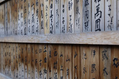 A wooden shrine wall in Japan with Kanji script Royalty Free Stock Photo