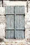 Wooden shutters, old window in stone wall Royalty Free Stock Image