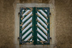 The wooden  shutters in a stone wall Stock Photos