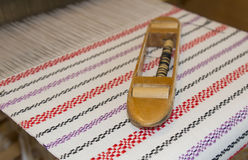 Wooden shuttle on woven fabric. Wooden shuttle on woven blanket Royalty Free Stock Image
