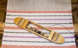 Wooden shuttle on woven fabric. Wooden shuttle on woven blanket Stock Images