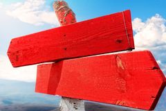Wooden sigh. Red wooden direction arrows on top of the mountain, against clear sky stock photography