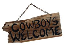 Wooden Sign. A wooden sign that says Cowboy's Welcome isolated on a white background Stock Photo