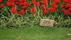 A wooden sign advising to Please keep off the grass, with green grass in the foreground and a flower bed with red flowers in the b royalty free stock photo
