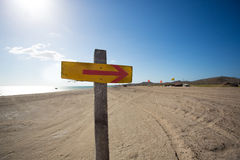 Wooden sign with an arrow and the beach in the backgound Royalty Free Stock Image