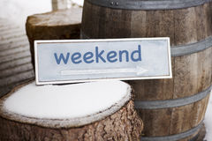 Wooden sign with arrow on tree stump with word Weekend royalty free stock image