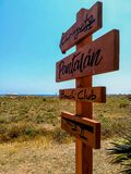 Wooden sign with arrows indicating the way to the beach. Of Puerto de Sagunto royalty free stock images