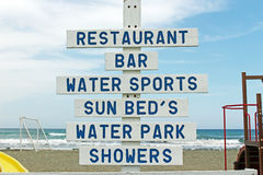 Wooden sign on the beach with sea in the backgroun Stock Images