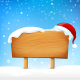 Wooden sign blank board and winter snow falling with copy space Royalty Free Stock Photography