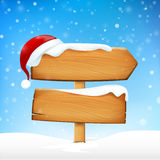 Wooden sign blank board and winter snow falling and Santa hat wi Royalty Free Stock Image
