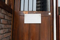 Wooden sign board hanging on door of cafe. Blank wooden sign board with rope hanging on door royalty free stock photo
