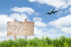 Wooden sign board  and Passenger airplane landing with green gra Stock Photo