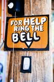 Wooden sign board. ring bell on the main door: For Help ring the bell Royalty Free Stock Photo