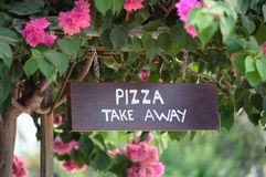 Wooden pizza take away sign board outside. Wooden sign board with text Pizza Take away outside with beautiful background of pink flowers and trees. Display Royalty Free Stock Images