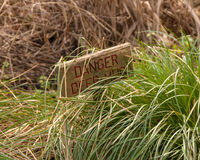 Wooden sign danger deep mud Stock Images