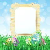 Wooden sign and Easter eggs on spring background Royalty Free Stock Photos