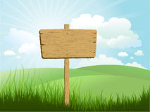 Wooden sign in grass. Against a blue sky Stock Photos