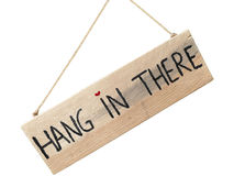 Wooden sign hang in there hanging on stone wall with heart as do Royalty Free Stock Photo