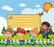 Wooden sign with happy children in garden Royalty Free Stock Photography