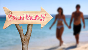 Wooden sign indicating to sun and beach Stock Photography