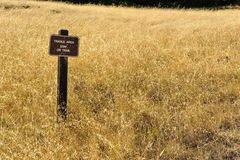 Wooden sign in middle of grass field Stock Images