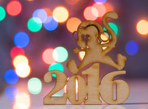 Wooden sign of monkey and incsription of 2016 year. With garland lights on background. Concept of Eastern horoscope Stock Photo