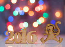 Wooden sign of monkey and incsription of 2016 year. With garland lights on background. Concept of Eastern horoscope Stock Photography