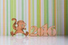 Wooden sign of monkey and incsription of 2016 year. On green striped background. Concept of Eastern horoscope Royalty Free Stock Photo