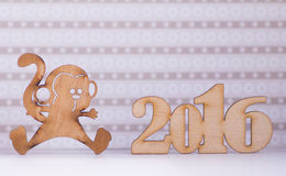 Wooden sign of monkey and inscription of 2016 year on lilac back Royalty Free Stock Photo