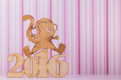 Wooden sign of monkey and inscription of 2016 year on pink strip Royalty Free Stock Images