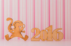 Wooden sign of monkey and inscription of 2016 year on pink strip. Ed background. Concept of Eastern horoscope Royalty Free Stock Photos