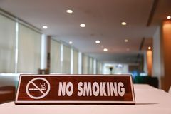 Wooden sign for no smoking. Wooden sign for no smoking on table in conference room royalty free stock image