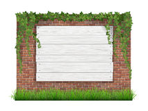 Wooden sign on a old brick wall background with green grass and Royalty Free Stock Photo
