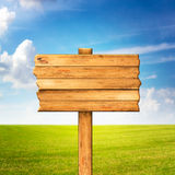 Wooden sign over beautiful green meadow and blue sky Stock Image