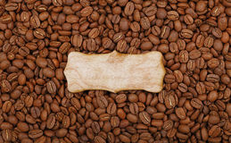 Wooden sign over roasted coffee beans. Blank rustic wooden sign over background of roasted brown Arabica coffee big beans pattern, close up, elevated top view Royalty Free Stock Images