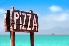 A Wooden Sign of Pizza on the sea coast royalty free stock images