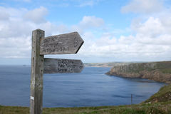 Wooden sign pointing the way along the dramatic clifftops of the coast path, Pembrokeshire, Wales Stock Photos