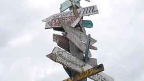 Wooden sign post arrows pointing to various cities and directions against sky. hd slowmotion. koh phangan, thailand. stock video