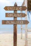Wooden sign post to bungalows and the pool on beach, Peru Stock Photo