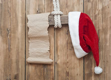 Wooden sign with Santa's hat. And blank paper scroll on a wooden background Stock Photos