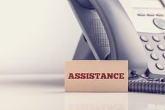 Wooden sign saying Assistance standing alongside a telephone Stock Photo