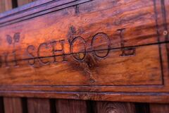 Wooden sign with the school inscription engraved on it