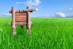 Wooden sign stands in the green grass Stock Photography
